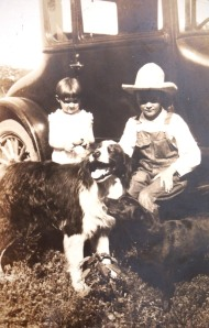 Lester and a young cousin with the farm dogs.